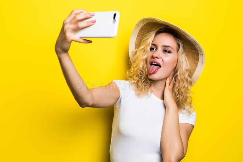 Ritratto della donna emozionante divertendosi mentre prendendo la foto del selfie isolata sopra fondo giallo immagini stock libere da diritti