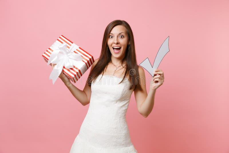 Ritratto della donna emozionante della sposa in scatola rossa del segno di spunta della tenuta del vestito da sposa con il presen immagine stock libera da diritti
