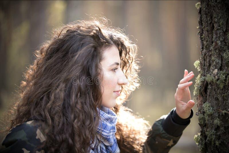 Ritratto della donna felice con capelli ricci in autunno che guarda all'albero Giovane donna di sorrisi ed allegra divertendosi d immagine stock