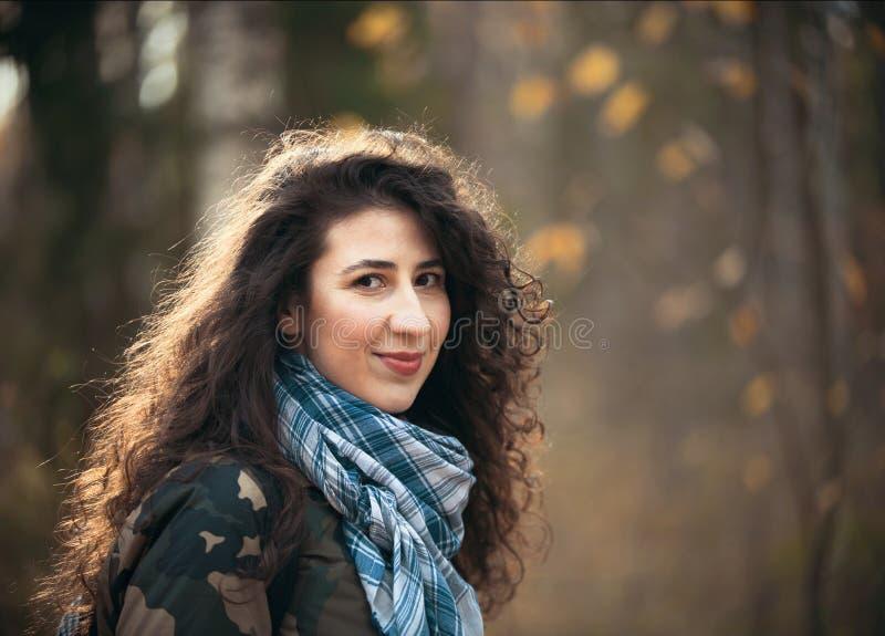 Ritratto della donna felice con capelli ricci in autunno che guarda alla macchina fotografica Giovane donna di sorrisi ed allegra immagini stock