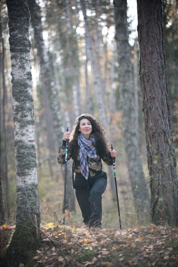 Ritratto della donna felice con capelli ricci in autunno che sta vicino all'albero Giovane donna di sorrisi ed allegra divertendo fotografia stock