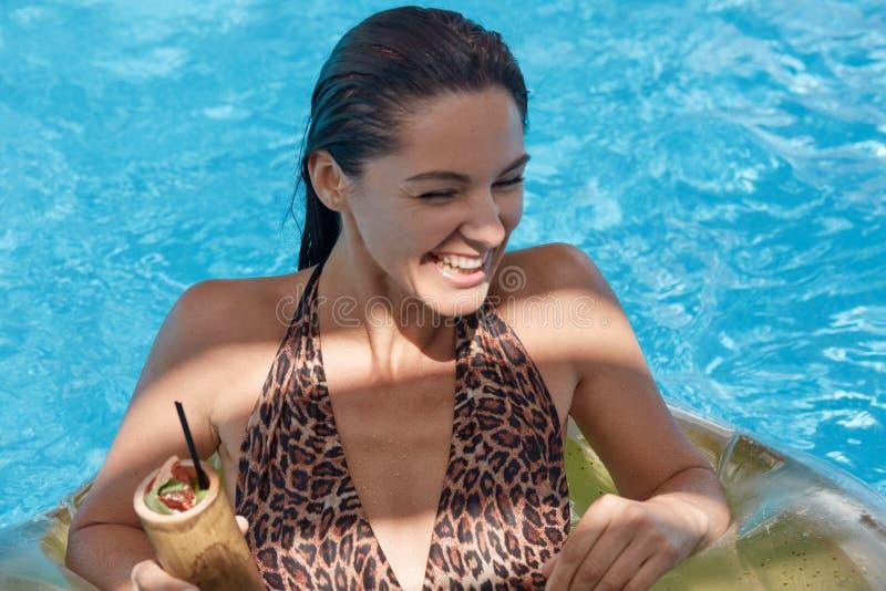 Ritratto della donna felice con capelli scuri bagnati, avendo resto in cocktail divertiresi e di bevanda della piscina, Bella rag immagini stock