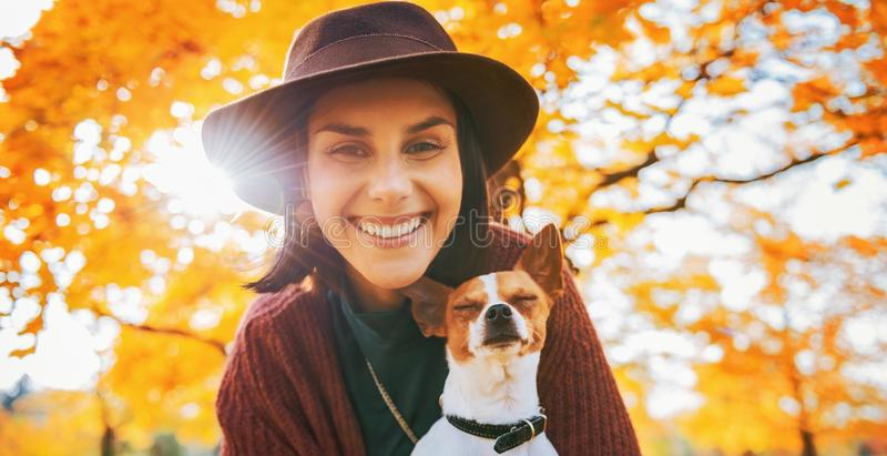 Ritratto della donna felice con il cane all'aperto in autunno immagine stock