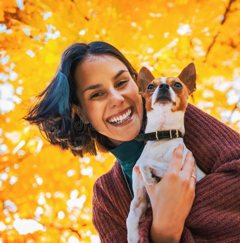 Ritratto della donna felice con il cane all'aperto in autunno fotografia stock
