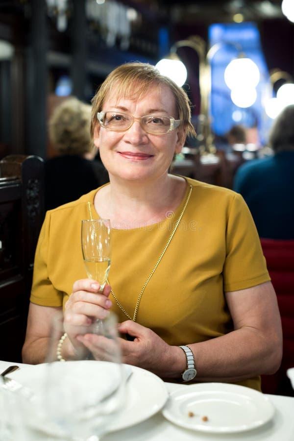 Ritratto della donna felice del pensionato che si siede in caffè fotografie stock libere da diritti