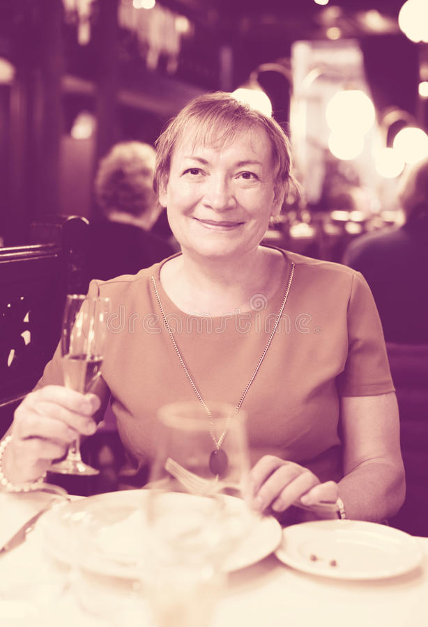Ritratto della donna felice del pensionato che si siede in caffè fotografie stock