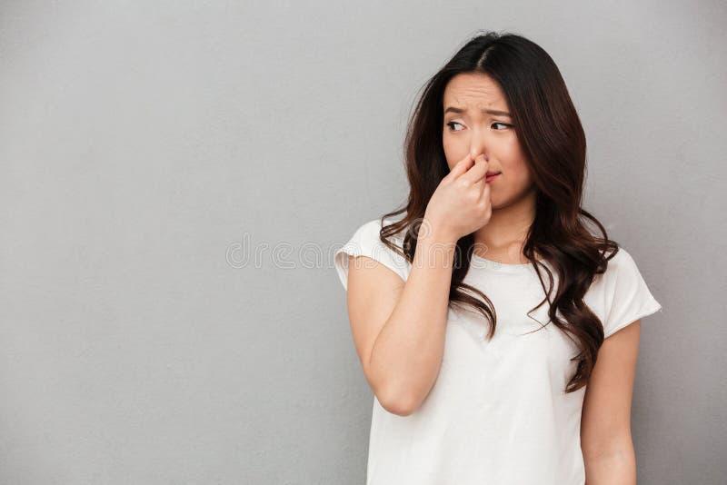 Ritratto della donna frustrata 20s che pizzica naso con repulsione sulla h fotografie stock libere da diritti