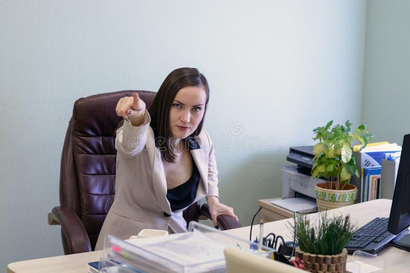 Ritratto della donna giovane arrabbiata e di grido di affari in una sedia di cuoio dietro la scrivania fotografie stock
