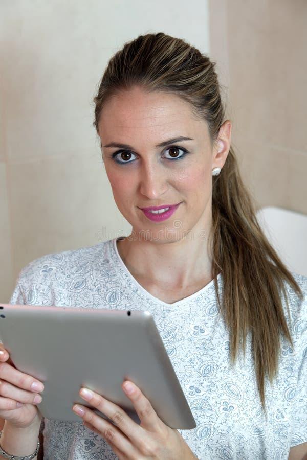 Ritratto della donna graziosa che per mezzo della compressa digitale per la compera da fotografia stock libera da diritti