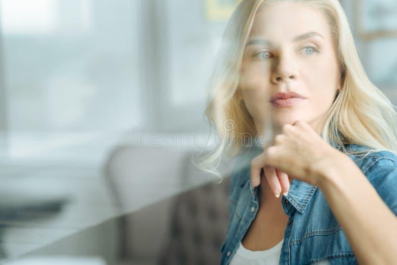 Ritratto della donna graziosa che si siede in un salone fotografie stock libere da diritti