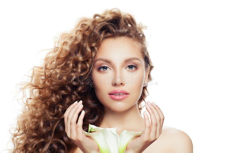 Ritratto della donna graziosa con capelli ricci lunghi, chiara pelle ed il fiore del giglio in sue mani isolate su fondo bianco immagini stock