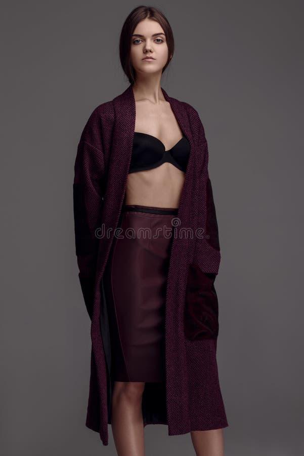 Ritratto della donna graziosa di Yong in cappotto di Borgogna, s di modo dello studio immagini stock libere da diritti