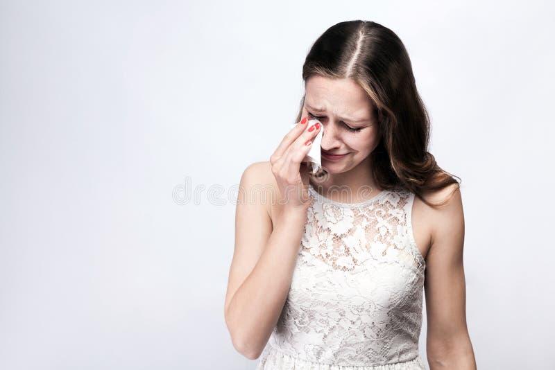 Ritratto della donna gridante triste e infelice con le lentiggini e vestito da bianco ed orologio astuto sul fondo di gray d'arge immagine stock