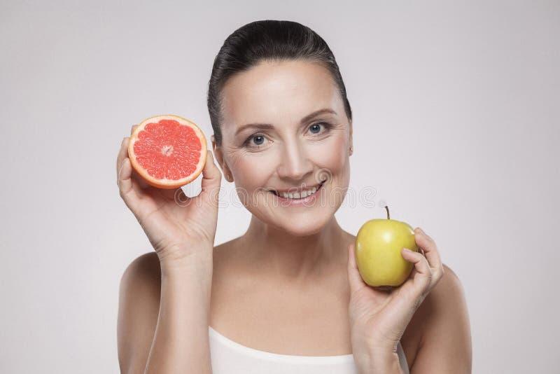 Ritratto della donna invecchiata media felice con sorridere a trentadue denti della pelle perfetta del fronte, tenendo il pompelm immagine stock