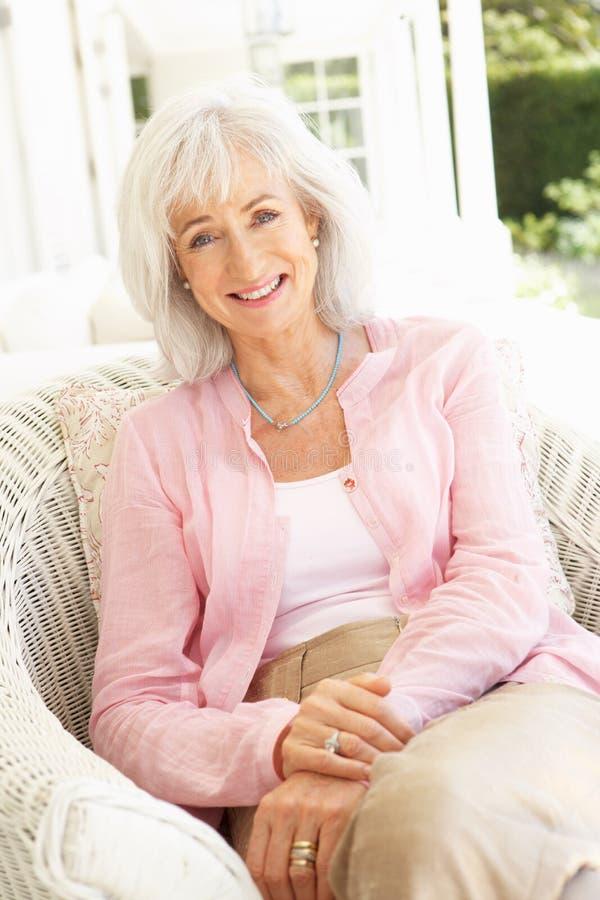 Ritratto della donna maggiore che si distende nella presidenza immagine stock