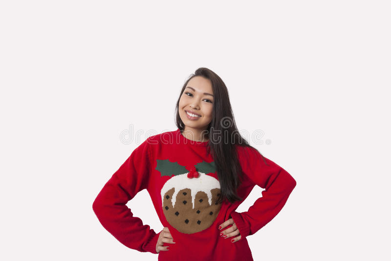 Ritratto della donna in maglione di Natale che sta con le mani sulle anche sopra fondo grigio immagini stock