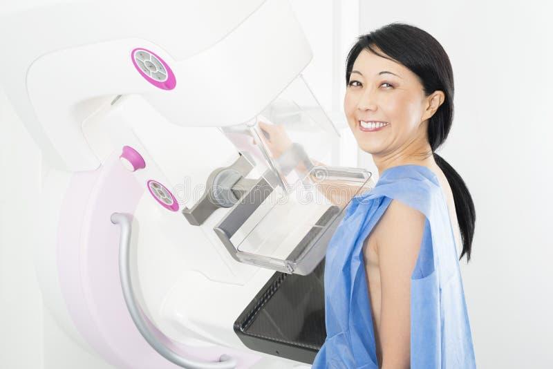 Ritratto della donna matura felice che subisce la prova dei raggi x di mammogramma immagini stock libere da diritti
