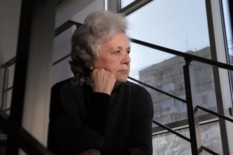 Ritratto della donna matura povera che si siede sulle scale fotografia stock libera da diritti