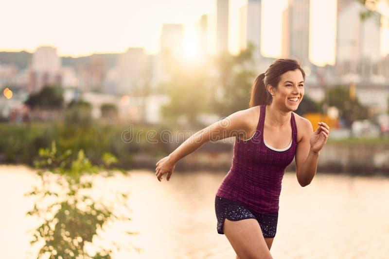 Ritratto della donna millenial attiva che pareggia al crepuscolo con un paesaggio urbano e un tramonto urbani nei precedenti fotografia stock libera da diritti