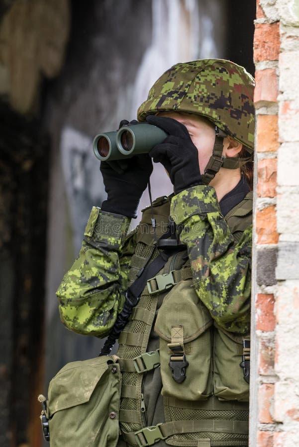 Ritratto della donna munita con cammuffamento Il giovane soldato femminile osserva con l'arma da fuoco immagine stock libera da diritti