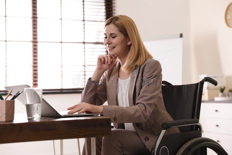 Ritratto della donna nel funzionamento della sedia a rotelle con il computer portatile fotografia stock libera da diritti
