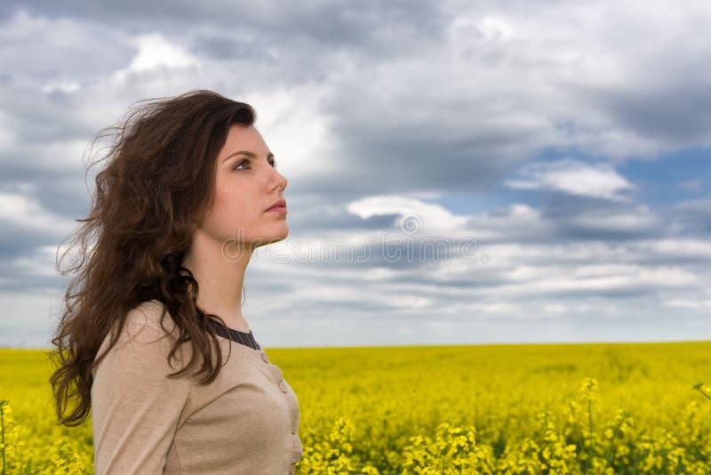 Ritratto della donna nel giacimento di fiore giallo immagine stock