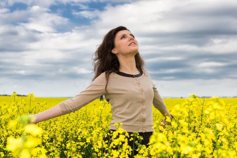 Ritratto della donna nel giacimento di fiore giallo immagine stock libera da diritti