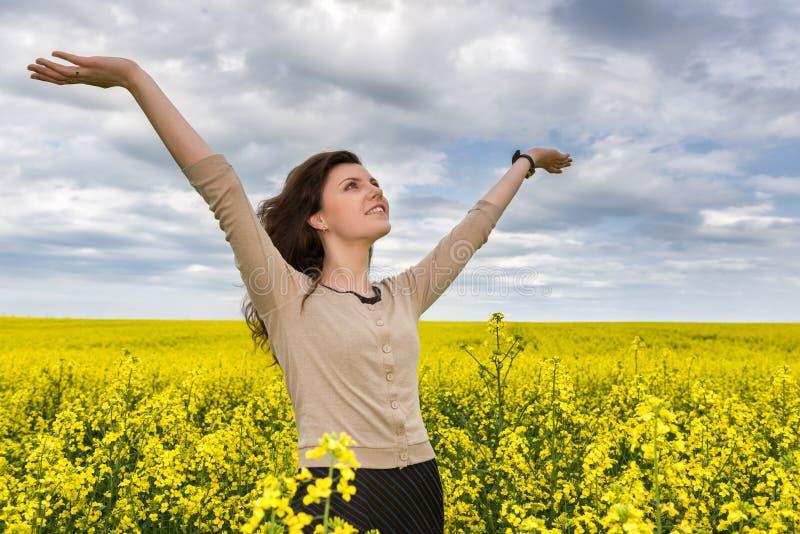 Ritratto della donna nel giacimento di fiore giallo immagini stock libere da diritti