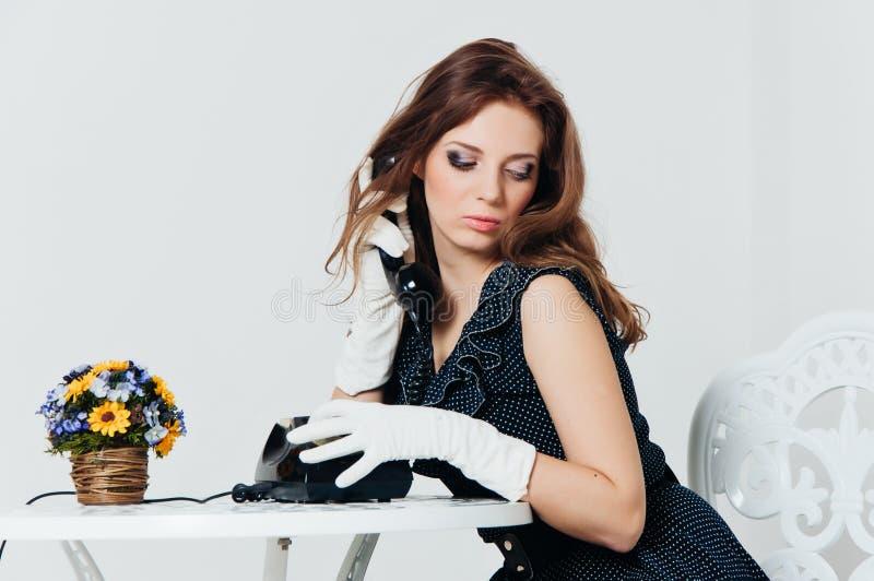 Ritratto della donna nel retro stile con il telefono fotografia stock