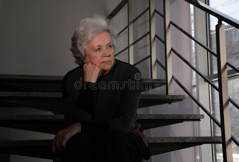 Ritratto della donna povera che si siede sulle scale fotografia stock libera da diritti