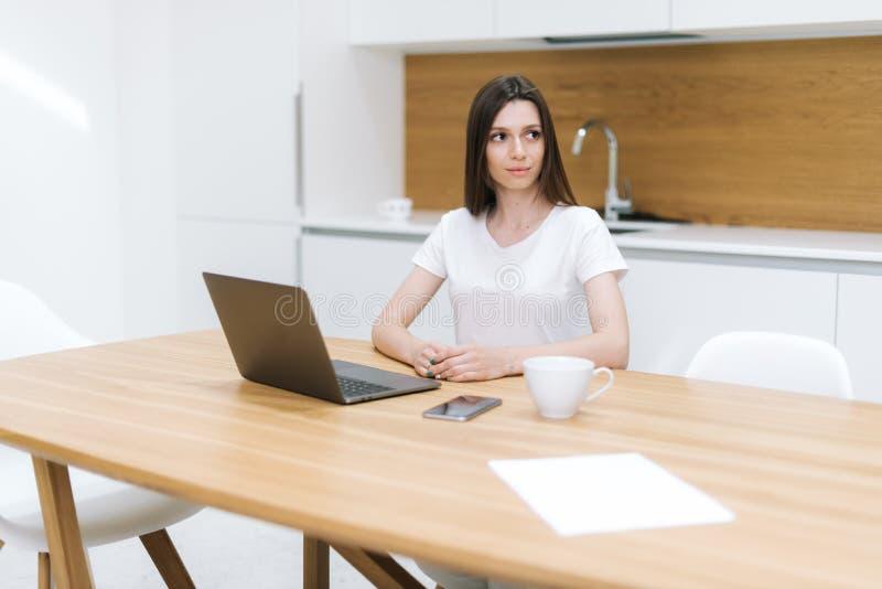 Ritratto della donna premurosa che si siede alla tavola ed a distogliere lo sguardo immagine stock libera da diritti
