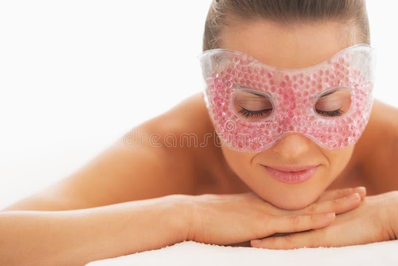 Ritratto della donna rilassata nella maschera di occhio che mette sulla tavola di massaggio fotografie stock
