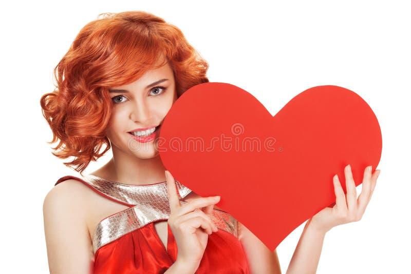 Ritratto della donna rossa sorridente dei capelli che tiene grande cuore rosso immagini stock