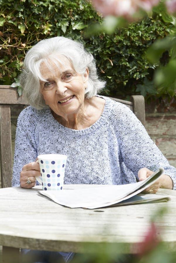 Ritratto della donna senior che si rilassa in giornale della lettura del giardino immagine stock