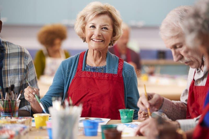 Ritratto della donna senior pensionata che assiste ad Art Class In Community Centre fotografia stock libera da diritti
