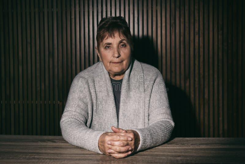 Ritratto della donna senior povera che si siede alla tavola fotografia stock libera da diritti