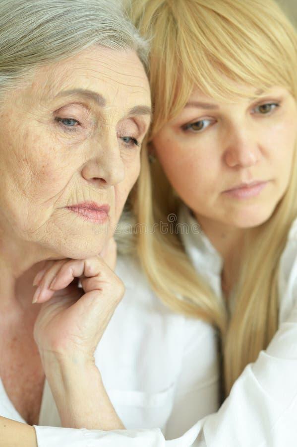 Ritratto della donna senior triste con la figlia immagini stock