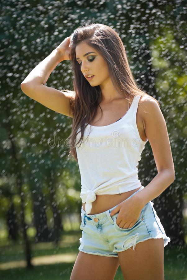 Ritratto della donna sexy in spruzzo di acqua con la maglietta bianca Ha una buona pelle delicata, posizione sensuale e sorride fotografia stock