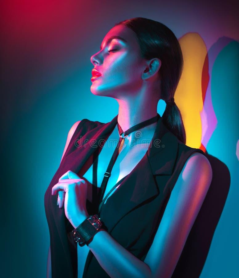 Ritratto della donna sexy in vestiti neri, accessori di modo, trucco luminoso alla luce al neon immagini stock