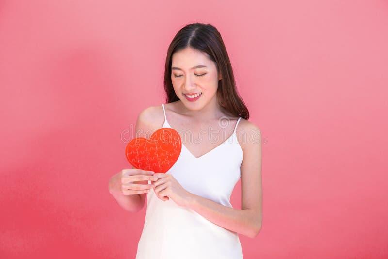 Ritratto della donna sorridente asiatica attraente che giudica il puzzle rosso della carta del cuore isolato su fondo rosa-rosso immagini stock libere da diritti