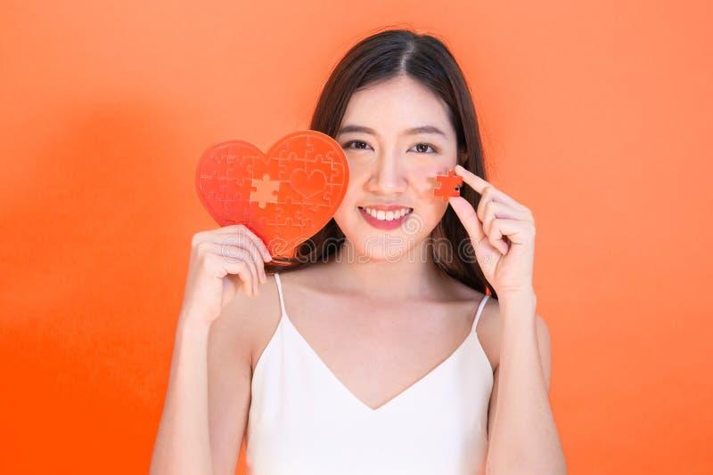 Ritratto della donna sorridente asiatica attraente che tiene il puzzle rosso della carta del cuore su fondo rosa-rosso fotografia stock libera da diritti