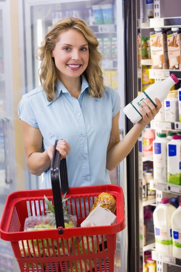 Ritratto della donna sorridente che ha sulle sue mani una bottiglia per il latte e un cestino della spesa freschi fotografie stock libere da diritti
