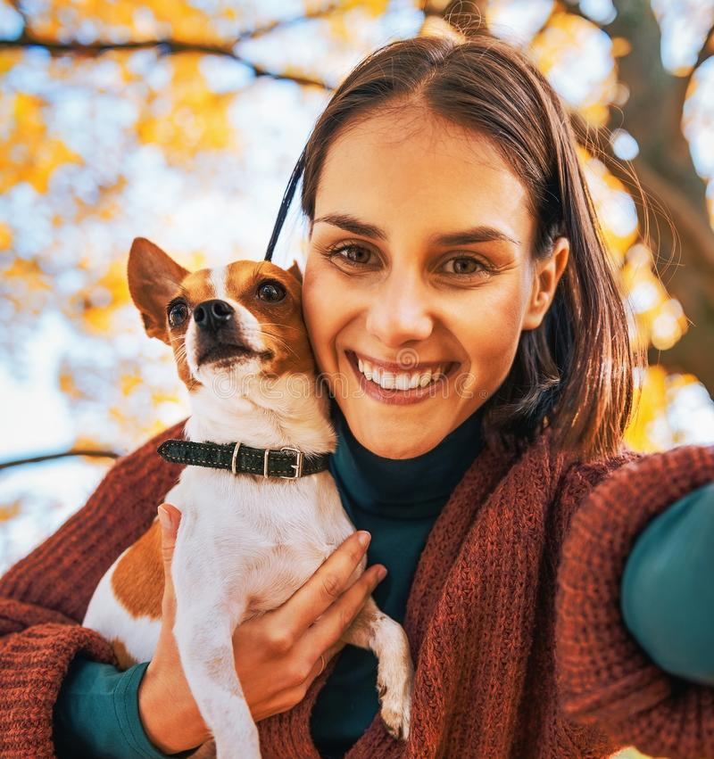 Ritratto della donna sorridente con il cane all'aperto che fa selfie immagini stock libere da diritti