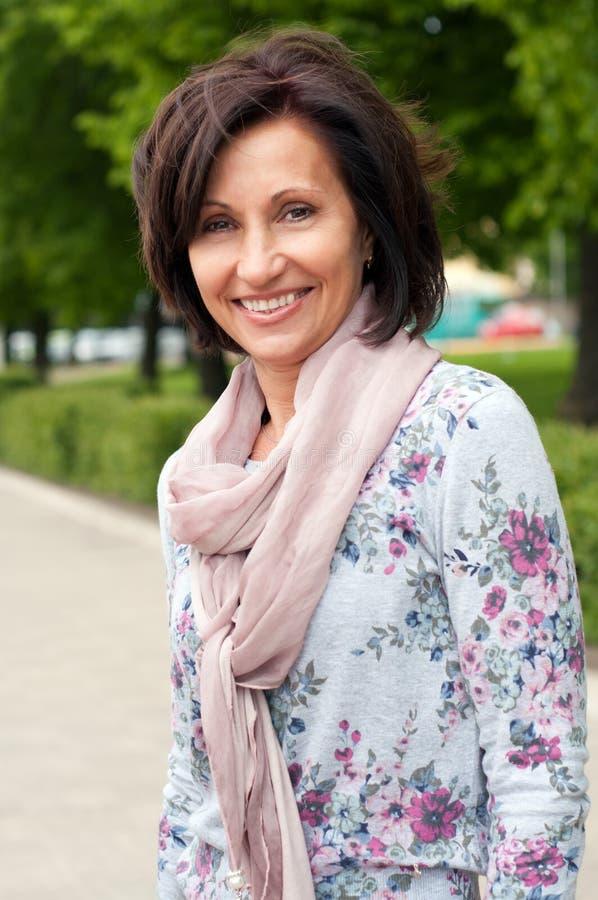 Ritratto della donna sorridente del brunette in sosta immagini stock libere da diritti