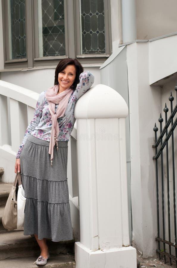 Ritratto della donna sorridente del brunette in vecchia città immagini stock