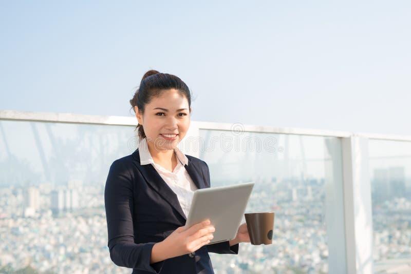 Ritratto della donna sorridente di affari che per mezzo del pc della compressa immagine stock libera da diritti