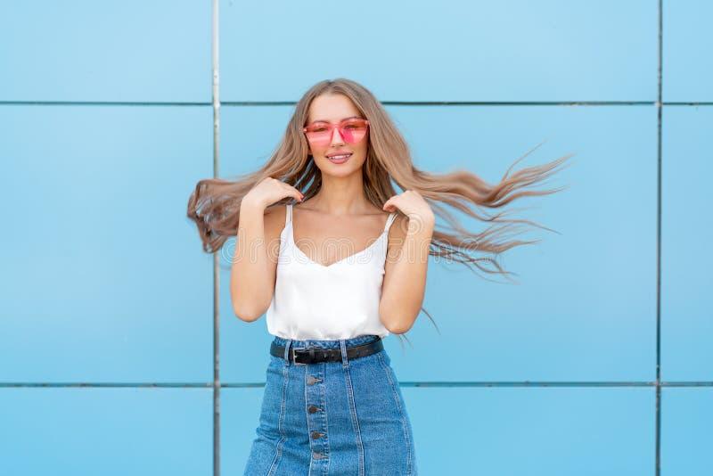 Ritratto della donna sorridente di modo di bellezza con l'acconciatura di volo, in occhiali da sole al neon rosa su fondo blu cas immagini stock libere da diritti