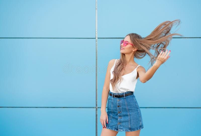 Ritratto della donna sorridente di modo di bellezza con l'acconciatura di volo, in occhiali da sole al neon rosa su fondo blu cas fotografie stock libere da diritti