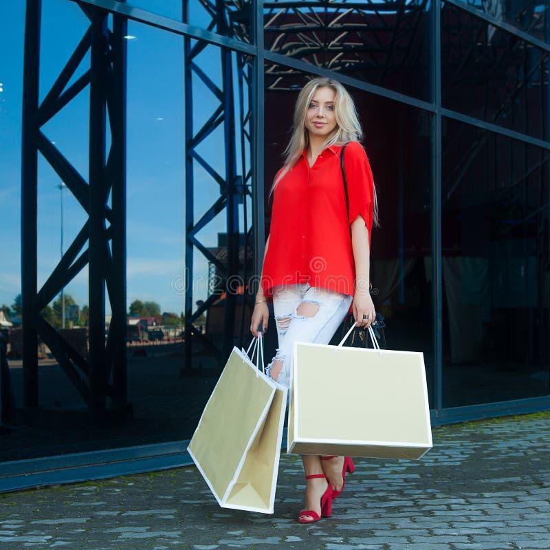 Ritratto della donna sorridente di modo di bellezza con i sacchetti della spesa in camicia rossa vicino al centro commerciale est fotografie stock libere da diritti
