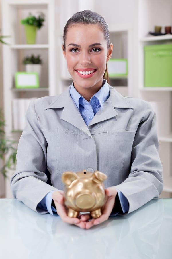 Ritratto della donna sorridente felice di affari, tenente divieto di porcellino dell'oro fotografia stock libera da diritti